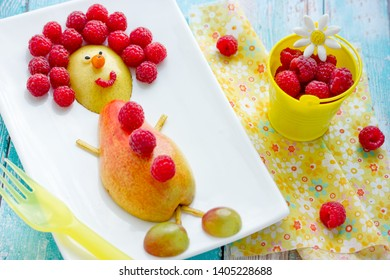 Food art idea for kids - pear and raspberry funny man, healthy snack from fruits and berries