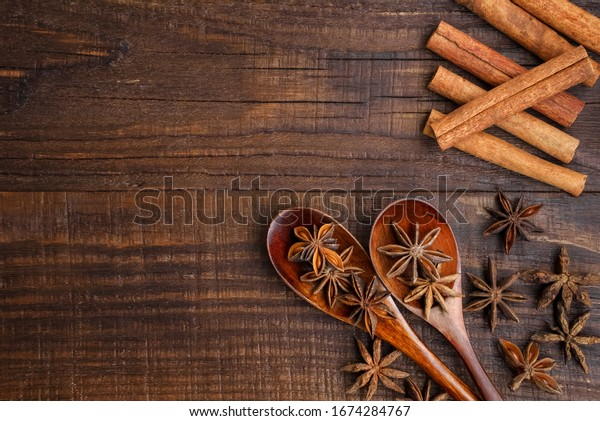 Food background. Anise stars in wooden spoons. Cinnamon sticks. View over.