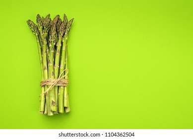 Food background asparagus flat lay pattern. bunch of fresh green asparagus on green background, top view.
