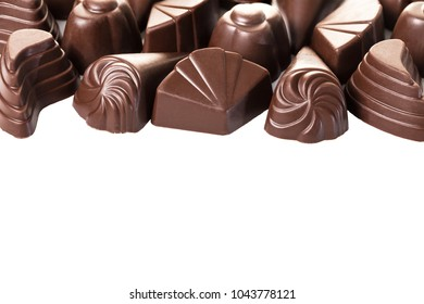 food background of assorted chocolates on white