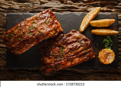 food background of BBQ barbeque pork ribs served with potato fried and baked corn, selective focus