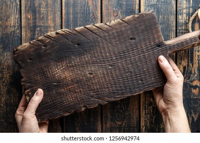 food background with blank space, woman's hands holding wooden cutting board above rustic wooden table top
