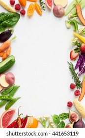 Food background border frame flat lay overhead of colorful fresh produce raw vegetables, carrot chilli cucumber purple cabbage spinach rosemary herb, plenty of copy-space in middle