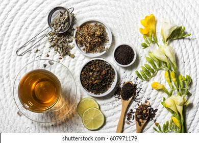 Food background with different black and green dry tea, rose buds cup of hot tea and iron teapot over dark wooden background. Tea drinking concept. Top view. Square image