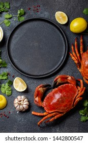 Food background with empty black plate, fresh crabs, lemons and herbs. Top view, copy space.