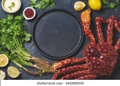 Food background with empty black plate, fresh king crabs, lemons and herbs. Top view, copy space.