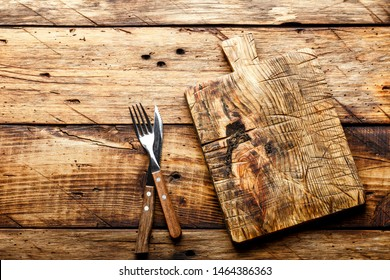 food background, empty cutting board served with a knife and fork on a rustic wooden table, view from the top