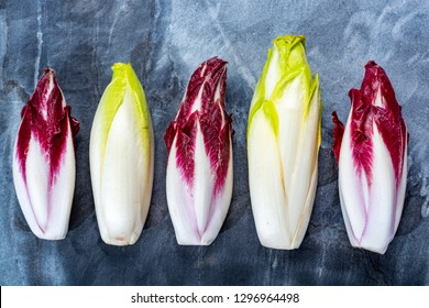 Food background, flat lay concept with fresh green Belgian endive or chicory and red Radicchio vegetables, also known as witlof salade