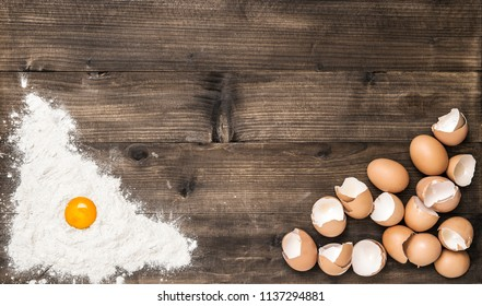 Food background. Flour and eggs on wooden kitchen table