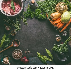 Food background frame with ingredients for tasty Ham Hock Soup : raw beef meat shin with bone, root vegetables, herbs and spices on dark rustic kitchen table with cooking spoon and cast iron pot
