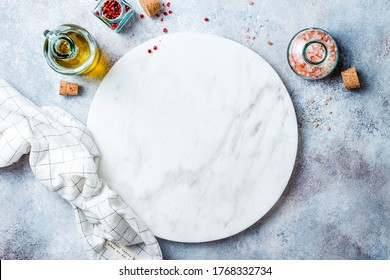 Food background with free space for text. Olive oil, spices around white marble board on light gray stone table. Healthy cooking concept with copy space. Top view.