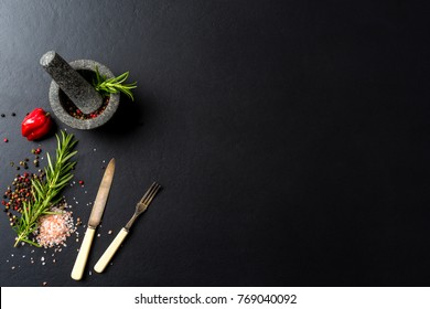 Food background with fresh herbs,  spices and stone mortar