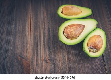 food background with fresh organic avocado on old wooden table, top view, copy space.