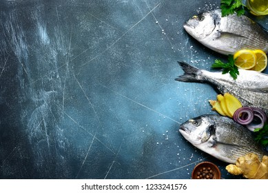 Food background with fresh raw dorado fish with ingredients for making on a dark blue slate, stone or concrete table.Top view with copy space.