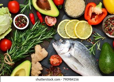 Food background. Fresh, raw Dorado with a swallow, lemon, avocado on a dark concrete background.