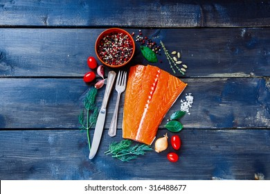 Food background with fresh salmon fish on dark wooden board. Fish with aromatic herbs, spices and vegetables - healthy food, diet or cooking concept.