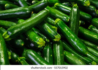 Food background - fresh and shiny zucchinis or courgettes