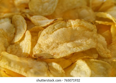 Food background with Gold ruffle potato chips. Selective focus. The horizontal frame.