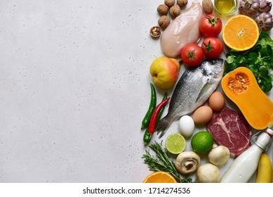 Arrière-plan cuisine avec des ingrédients biologiques sains et propres du menu paléo sur une table en ardoise grise, en pierre ou en béton. Vue de dessus avec espace de copie.