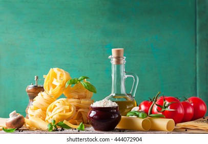 Food background or healthy concept with olive oil, fresh basil, pasta tagliatelle, rice, mushrooms and pepper on a wooden background, horizontal with copy space