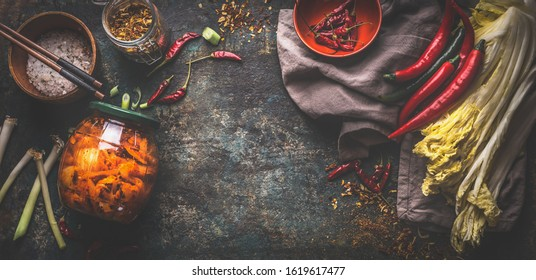 Food background with homemade kimchi in jar, fermented chinese cabbage in hot chili sauce with ingredients. Top view. Banner. Frame
