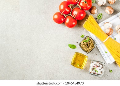 Food background, ingredients for cooking dinner.  Pasta spaghetti, vegetables, sauces and spices, grey stone background copy space top view