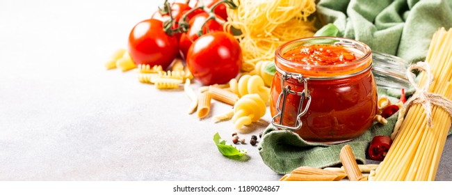Food background with ingredients for italian healthy homemade classic spicy tomato pasta or pizza sauce with assorted pasta, pine nuts and basil. Copy space. Banner.