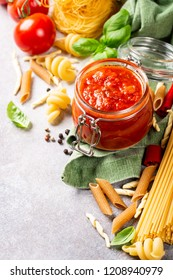 Food background with ingredients for italian healthy homemade classic spicy tomato pasta or pizza sauce with assorted pasta, pine nuts and basil. Copy space.