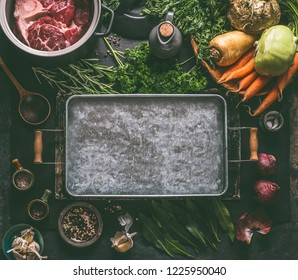 Food background. Ingredients for tasty Ham Hock Soup : raw beef meat shin with bone, root vegetables, herbs and spices around tray on dark rustic kitchen table with cooking spoon and cast iron pot