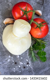 Food background with mozzarella, tomatoes, garlic cloves, herbs and spices.  Top view on slate.