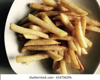 Food background / Potato slices are coated in garlic salt and sugar and baked into crispy, golden French fries.