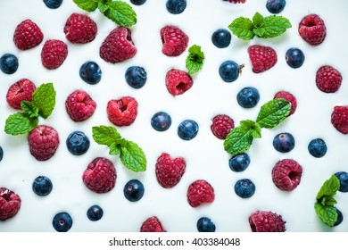 Food background, raspberries and blueberies on yoghurt. From above flat lay design.