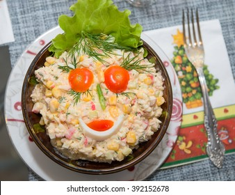 Food background - salad olivier close-up. Green peas, cucumber, potatoes, sausage, mayonnaise. Decoration in the form of a face from tomatoes