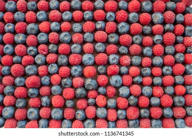 food background - Tart with blueberries and raspberries, checkerboard pattern. rotational decorated in a glass form. view from above