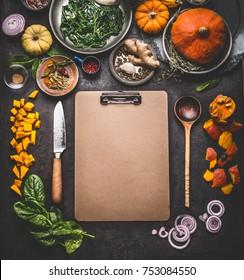 Verpflegungshintergrund für schmackhafte Winter- und Herbstspeisen mit Kürbis. Verschiedene Kochzutaten mit Löffel und Messer um leere Karton-Zwischenablage für Speisen oder Rezepte, Draufsicht, Rahmen, Mockup