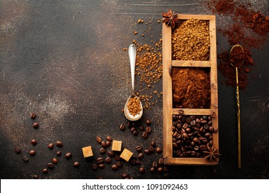 Food background with three kinds of coffee: beans, milled, instant in wooden box on old concrete brown background. Rustic stile. Selective focus. Top view.