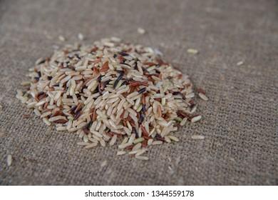 Food background with three mixed of Thai rice varieties : brown rice, mixed wild rice, white (jasmine) rice. species Oryza sativa