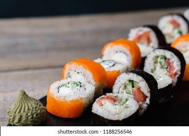 Food background, traditional Japanese meals, restaurant menu. Tasty appetizing maki sushi rolls with salmon served on wooden tray, copy space