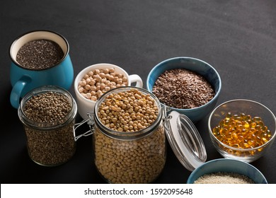 Food background. Various seeds and grains- Source of omega 3 foods. Fish oil, chickpeas, soybeans, hemp seeds, chia, sesame seeds, flax seeds. Omega 3 background.