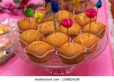Food, baking and holidays concept - cupcakes or muffins with halloween party decorations and candies on plate.