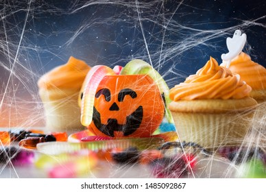 food, baking and holidays concept - cupcakes or muffins with halloween party decorations, jack-o-lantern, jelly worm candies and spiderweb on wooden table over starry night sky background