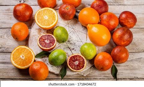 Lebensmittelbanner-Format. Auf einem Holztisch stehen saftige rote Orangen, Zitronen und Limetten. Saisonale Zitrusfrüchte