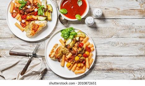 Lebensmittelbanner. Putenfilet gegrillt, Penne Nudeln mit Tomaten, Gewürze, Parmesan-Käse und frischer Basilikum. Tomatensauce. Traditionelle italienische Küche. Zwei Servietten auf Holzhintergrund. Leerzeichen kopieren