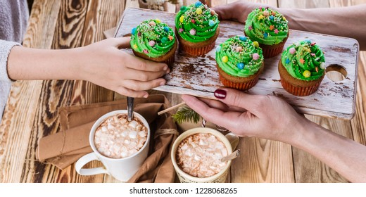 Food banner. Women's and children's hands are holding Christmas muffins in the form of green Christmas trees