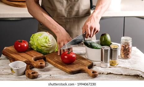 Lebensmittelbanner. Ein junger Küchenchef in brauner Schürze verwendet ein Küchenmesser, um Gemüse für einen köstlichen vegetarischen Salat zu schneiden. Kochen Sie leckeres und gesundes Essen in der Hausküche. Freshnes und leckeres Essen.