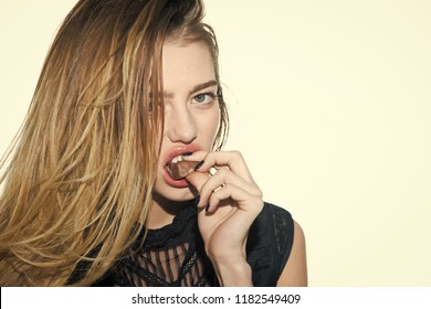Food and beauty, healthy lifestyle. Dieting and fitness, calorie. Temptation and enjoyment, weight. Woman with long hair eat chocolate isolated on white. Sexy girl with no makeup bite candy