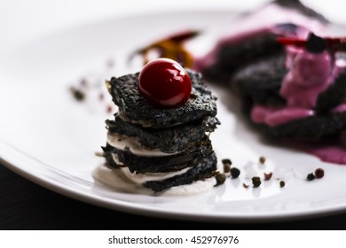 Food and beverages - shooting in the studio. Black cherry cake with pink cream. Delicious pastries.
