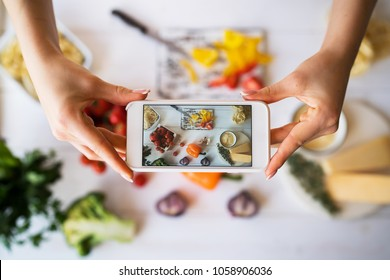 Food blogger concept. Young woman recording video on smartphone at kitchen. Woman recording every step of cooking process for her blog. Diet, technology, health, food, cooking, culinary, and people.