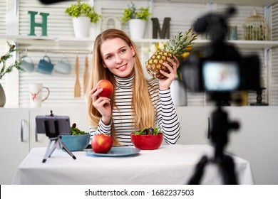Food blogger cooking fresh vegan salad of fruits in kitchen studio, filming tutorial on camera for video channel. Female influencer holds apple, pineapple and talks about healthy eating. Fructorianism