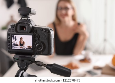 Food blogger recording video indoors, focus on camera display. Space for text